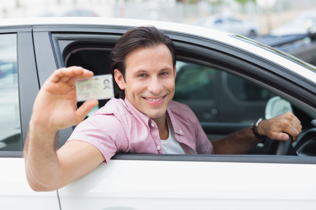 man-smiling-holding-his-driving-